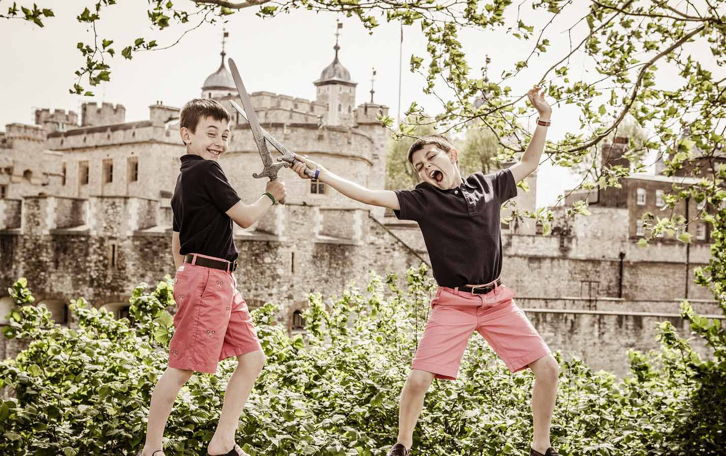 Boys play fighting with swords infront of a castle.